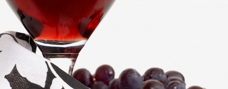 A low view of a wine glass with wine and grapes and napkin